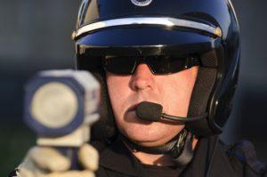 12062493 - a police officer pointing his radar gun at speeding traffic.
