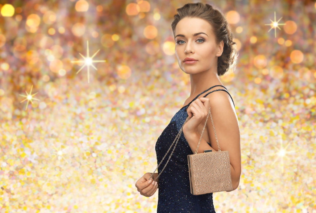 48853969 - people, holidays, luxury and glamour concept - woman in evening dress with small handbag over golden lights background